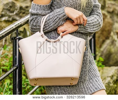 Fashion Woman In Trendy Outfit Grey Pullover Jumper Outdoor. Female Model Holding Bright Bag Handbag