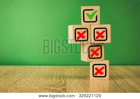 Wooden Cubes With The Image Of Check Marks Marks On A Green Background.
