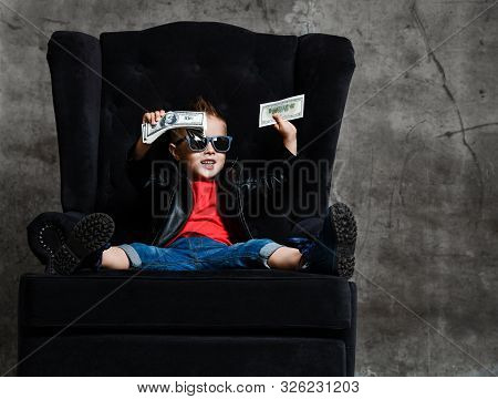 Cheerful Rich Kid Boy In Sunglasses, Leather Jacket And Red T-shirt Is Sitting In Big Luxury Armchai