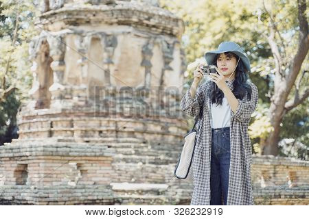 Young Asian Female Traveler Taking A Photo With Retro Camera While Traveling In Popular Tourist Attr