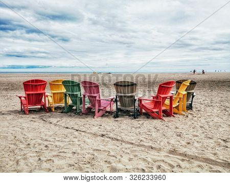Eight Many Colorful Red, Brown And Yellow Wooden Muskoka Adirondack Chairs In Row On Beach Outside.