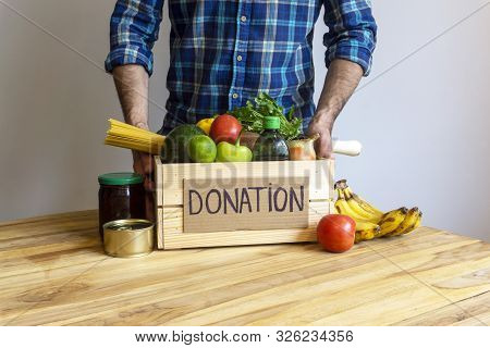 Food Donation Concept. A Man Holding A Donation Box With Vegetables, Fruits And Other Food For Donat