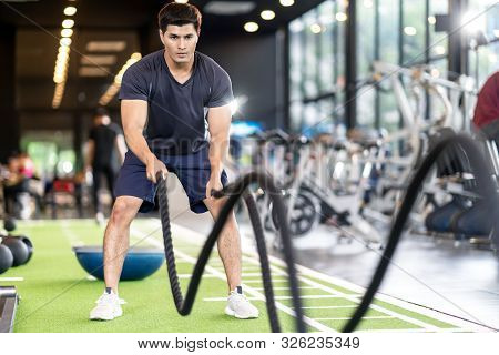 Sporty Asian Man Exercising With Battle Ropes At The Gym On Green Floor. Strong Male Determine With