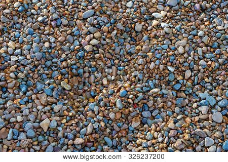 Pebble Beach Texture With Simple Surface. High Resolution Photo. Empty Colorful Small Pebble And Sto