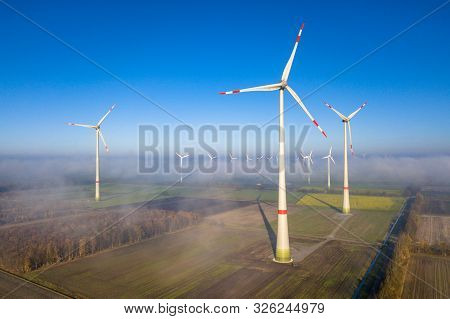 Aerial View Of Wind Turbines In Windfarm Above Mist Layer In German Countryside In The Morning Sun.