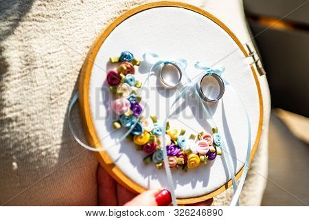 Close-up View Of Golden Wedding Rings On Decorative Stiching Ring Pillow