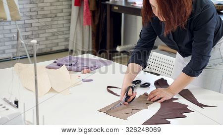 Cutting And Sewing Products In Tailoring Business. Tailor Woman Cutting Details From Fabric Works In