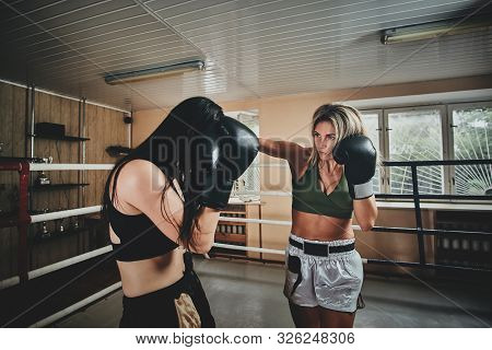 Boxing Coach And Her Trainee Have A Sparring On The Ring At Special Gym.