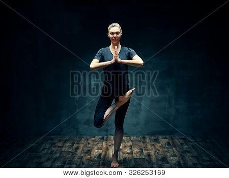 Young Beautiful Woman Doing Yoga Asana Half Bound Lotus Tree Pose In Dark Room. Wellbeing, Meditatio