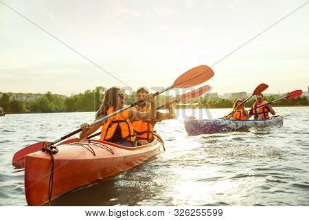 Happy Young Caucasian Group Of Friends Kayaking On River With Sunset In The Backgrounds. Having Fun