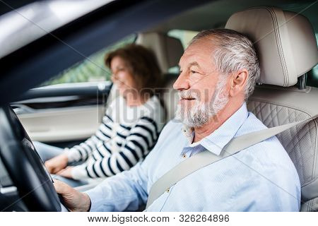 Happy Senior Couple With Smartphone Sitting In Car, Driving, .