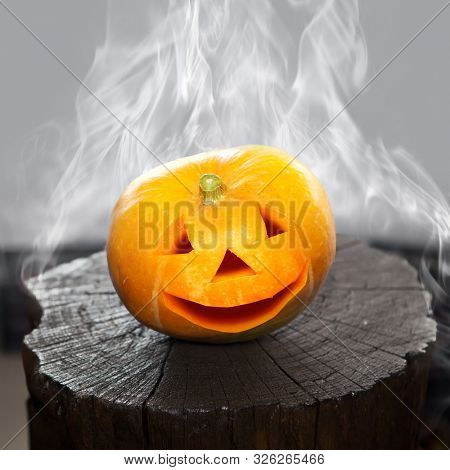 Pumpkin that laughs on a charred stub in smoke. Scenery for Halloween holiday. poster