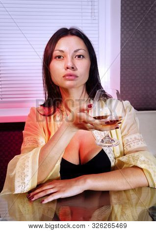 beautiful sad girl with glass of brandy in cafe