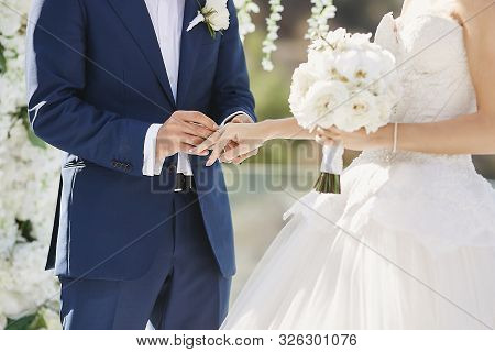 Hands With Wedding Rings. Modish Groom Putting A Golden Ring On The Brides Finger During The Wedding