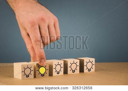 The Hand Makes A Choice And Chooses A Burning Light Bulb, A Symbol Of A Fresh Idea