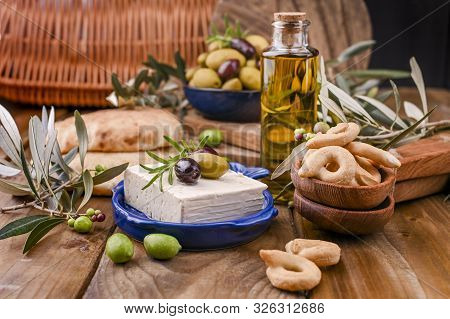 Greek Cheese Feta With Thyme And Olives, Selective Focus. Bread And Young Olives Branch On Olive Boa