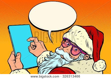 Santa Claus With A Tablet. New Year And Christmas Online Sales Concept. Merry Christmas And Happy Ne