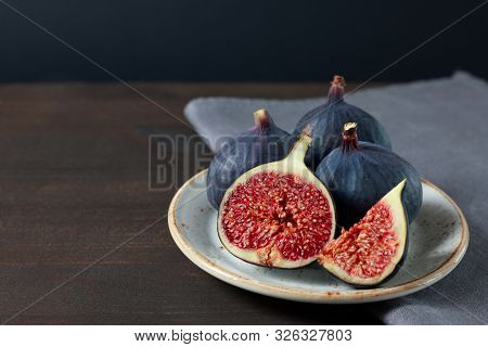 Fresh Figs In A White Plate On A Dark Background. Copy Space. Purple Ripe Sliced And Whole Figs On A