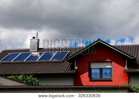 Solar Panels On The Roof Of A House In Cloudy Weather. Storm Clouds Block The Sunlight. The Concept