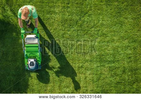 Lawn Moving Aerial Photo. Caucasian Gardener With Gasoline Grass Mower At Work. Landscaping Business