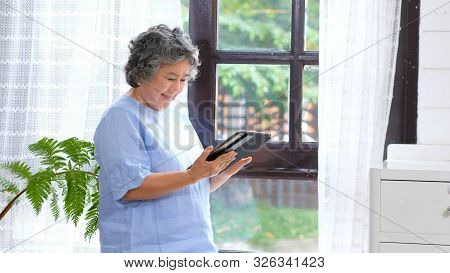 Senior Asian Woman Using Digital Tablet Computer At Home Background, Retirement Asian Woman And Digi