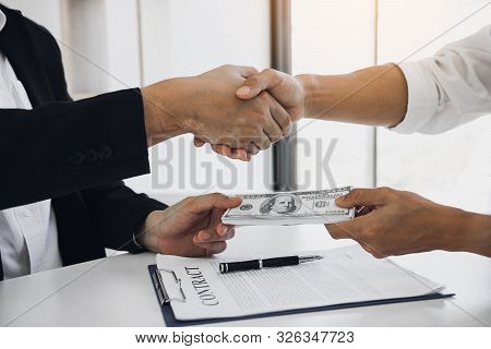 Two Corporate Businessmen Shaking Hands While One Man Places Money On Document In Office Room With C