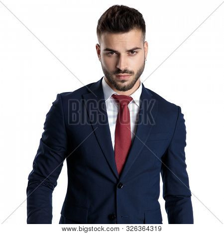 Tough young businessman wearing a blue navy suit and red tie while walking on white studio background