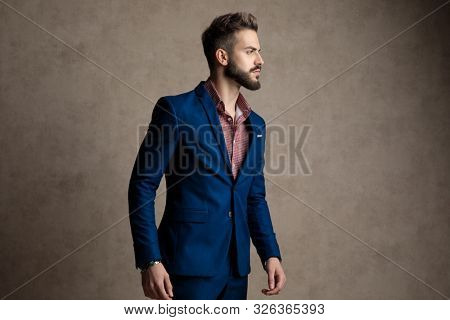 portrait of a handsome formal business man wearing a navy suit standing and looking to a side curious against gray studio background