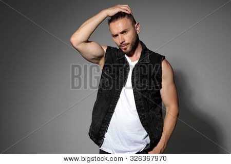 Confident tough man adjusting his hair and holding his hand in his pocket while wearing a black jeans vest, standing on gray studio background