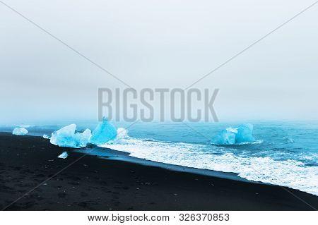 Blue Ice On The Jokulsarlon Ice Beach, Southern Iceland. Beautiful Coast Of Atlantic Ocean With Blac