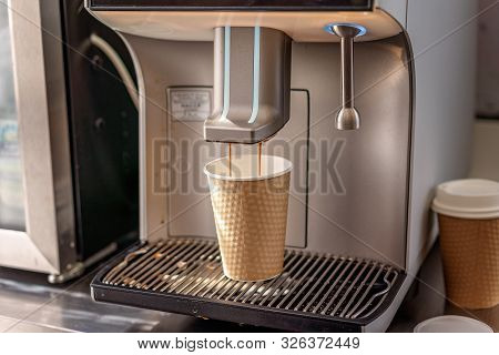 An Automated Espresso Coffee Making Machine Expelling A Cappuccino Into A Paper Takeaway Cup