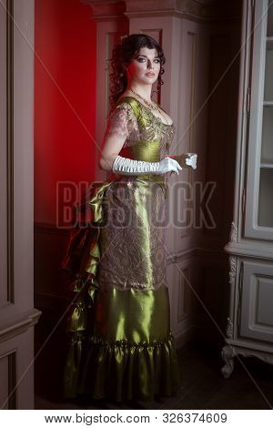 Woman In Retro Style, Her Beautiful Dress Is Olive Color.