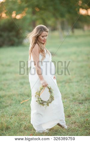Portrait Of A Pregnant Woman In The Sun. Young Beautiful Pregnant Woman With A Wreath On Her Head In