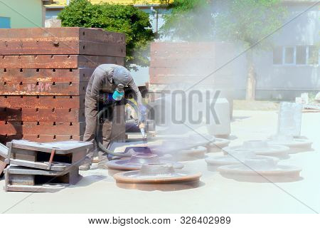 Sandblasting At An Industrial Plant, A Worker Knocks Down Oxide And Dirty Rust With Sand Under Air P