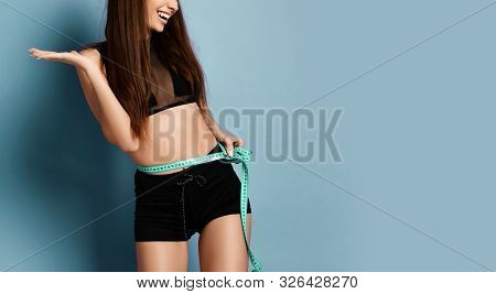 Closeup Of Happy Sporty Girl In Shorts And Sport Bralet With A Measure Tape Around Her Waist Holding