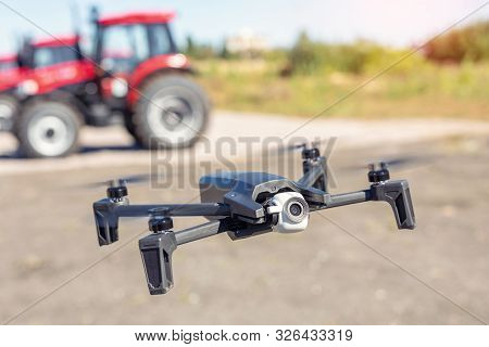 Compact Black Drone Quadcopter With Surveillance Camera Flying Low Against Red Agricultural Tractor