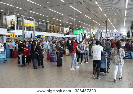 Amsterdam, Netherlands - July 11, 2017: Travelers Visit Schiphol Airport In Amsterdam. Schiphol Is T