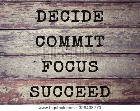 Motivational And Inspirational Wording - Decide, Commit, Focus, Succeed Written On Wooden Planks. Bl