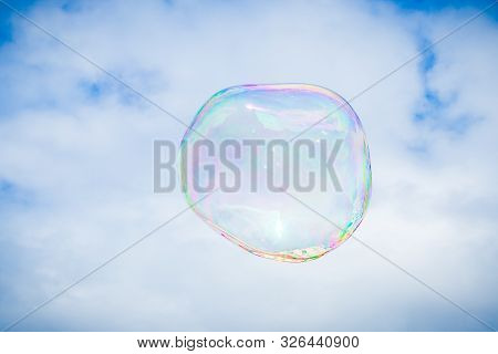 Big Bubble Of Bubble Maker Flying In The Air On Sky Background