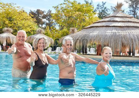 Cheerful group of seniors has fun in the pool and keeps their fingers crossed