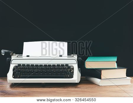 Vintage Typewriter And Stack Of Books On Rustic Wooden Desk Against Black Background, Content Creati