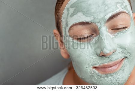 Closeup portrait of a nice female with blue clay mask on face, anti acne or anti age spa treatment, healthy skin, gray background