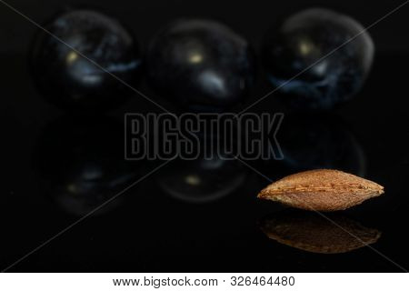 Group Of Two Whole Fresh Purple Plum With One Drupe Isolated On Black Glass