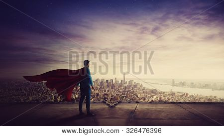 Rear View Confident Businessman, Red Cape Suit, As Hero Stands On The Rooftop Of A Skyscraper Lookin