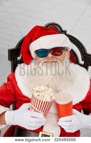 Authentic Santa Claus In 3d Glasses Snoozing In Comfortable Armchair With Popcorn And Cola In Hands.