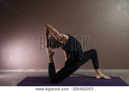 Young Sporty Man Practicing Yoga, Meditating In Yoga Pose, Working Out, Wearing Sportswear, Indoor F