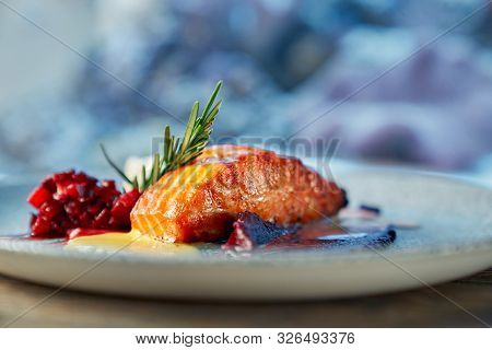 Closeup Of Piece Of Delicious Red Salmon Served With Fruit Garnish On Plate In Restaurant. Healthy D