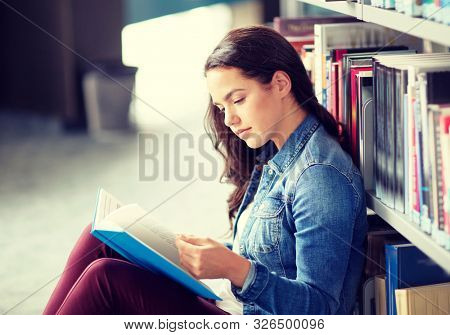 education, high school, university, learning and people concept - student girl reading book sitting on floor at library