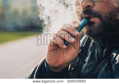 Man Smokes New Vape Pod System, Inhales And Exhales Vapor Of Electronic Cigarette, Vaping Concept, S