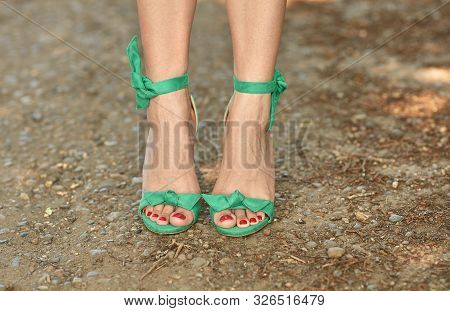 Well-groomed Female Legs In Summer Sandals With Heels. Green Lace-up Sandals. Luxury Vintage Sandals